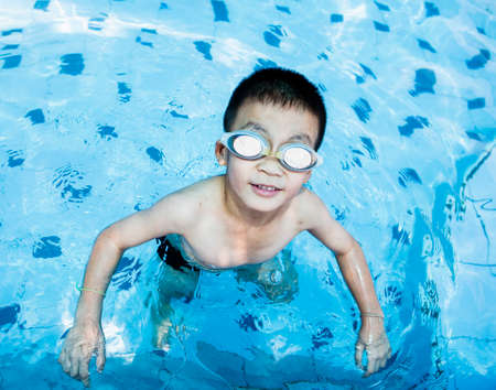 pool diving: Cute boy swimming and playing in water in swimming pool