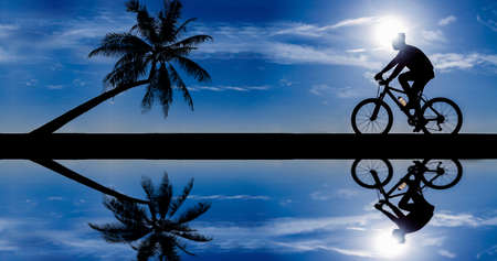 silhouette of cyclist in motion on the background of a beautiful blue sky  photo
