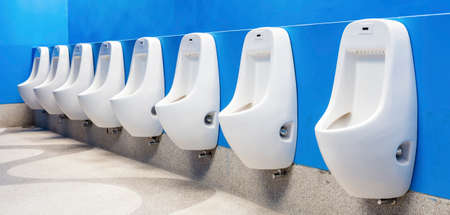 Line of white porcelain urinals in public toilets