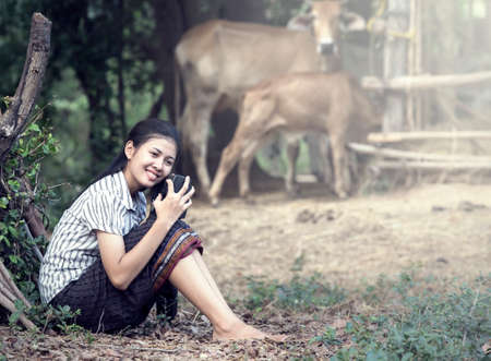 Thai Young Woman Holding Radio in farm photo