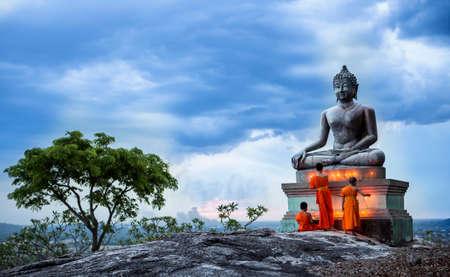 buddha image: Yong buddhist monk fire candles to the Buddha Stock Photo