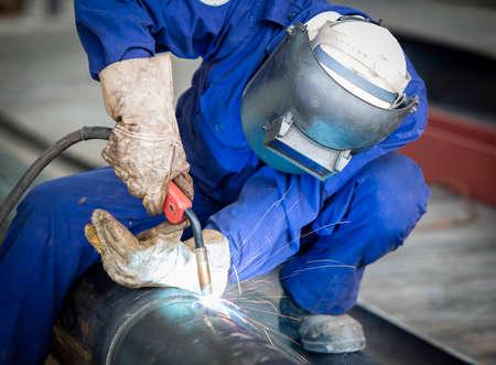 soldador: Trabajador con la máscara protectora de soldadura de metal Foto de archivo