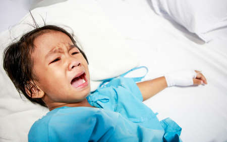 child patient: Sick little girl crying in hospital bed Stock Photo