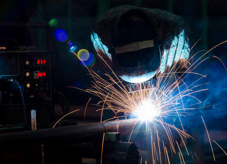 Worker with protective mask welding metal photo