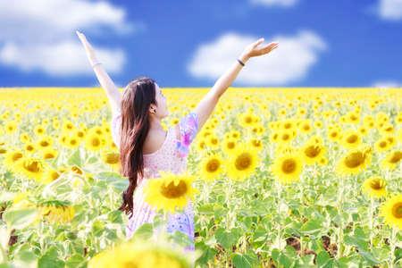 alabando a dios: Chica de verano sin preocupaciones feliz en campo de girasol en la primavera.