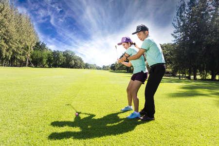 若い女性のゴルフ プレーヤー ゴルフのプロとドライビング レンジで、彼女はおそらくは運動します。