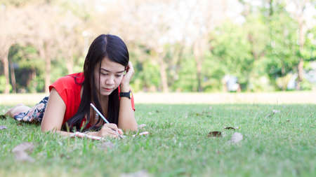 field study: Beautiful young woman with note at outdoor