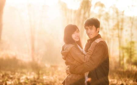 jovenes enamorados: Feliz pareja tener mucho tiempo juntos - fotografiado al amanecer contra el sol Foto de archivo