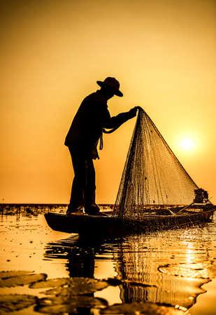 ときに釣り、タイのアクションで湖の漁師 写真素材