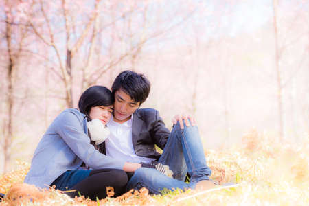Portrait of beautiful young couple sitting on ground in park relaxing photo