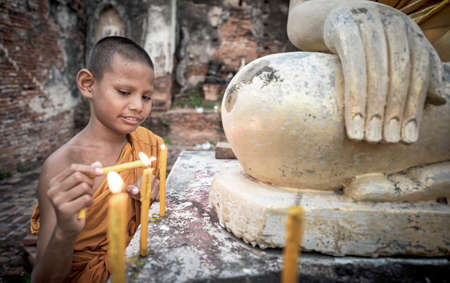 novice: Novice Monk fire candles to the Buddha Editorial