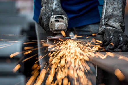 welding mask: Industrial worker cutting metal with many sharp sparks Stock Photo