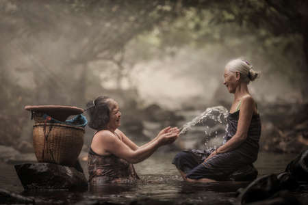 pobre: Vieja mujer asiática en la cascada