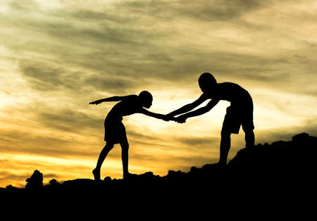 Teamwork boy hiking help each other trust assistance silhouette in mountains, sunset.