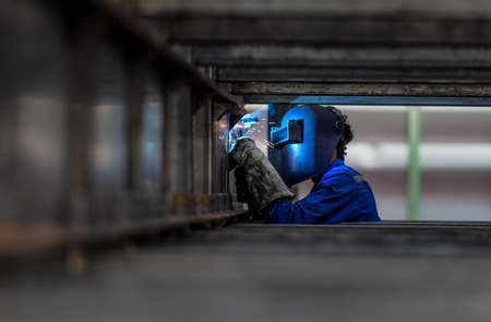 Worker with protective mask welding metal