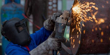 working hands: Electric wheel grinding on steel pipe in factory Focus on Tool