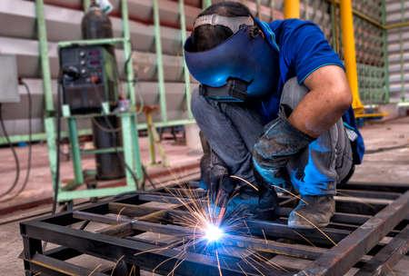 steel workers: Worker with protective mask welding metal