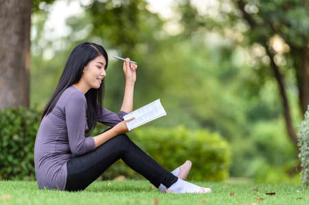 Portrait of happy charming Thai woman reading a book outdoors