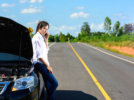 call for help: Young girl with broken down car with hood open call for help Stock Photo