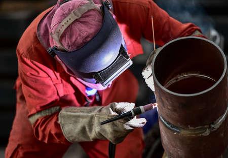 welding mask: Welder in factory with protective equipment welding pipe