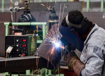 welding mask: Welder in factory with protective equipment welding pipe