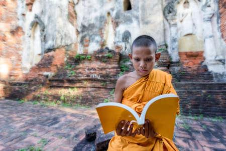 Novice monk reading outdoors, sitting outside monastery, Thailand Stock Photo
