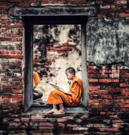 Zuidoost-Aziatische Novice monnik lezen boek buiten het klooster, de boeddhistische leer. Stockfoto