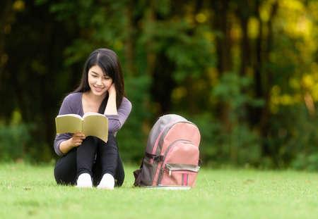 mujer leyendo libro: Retrato de feliz encantadora mujer tailandesa de leer un libro al aire libre Foto de archivo