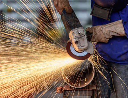 steel structure: Electric wheel grinding on steel structure in factory (Low speed shutter) Stock Photo