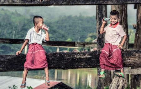 amistad: muchachos asi�ticos hablando por un tel�fono lata