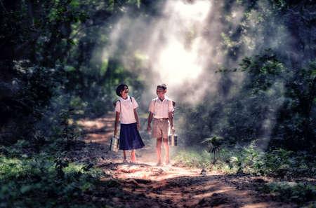Estudiante pequeño muchacho asiático y una niña, campo en Tailandia