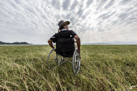 desire: Man on a wheelchair relaxing in a park Stock Photo