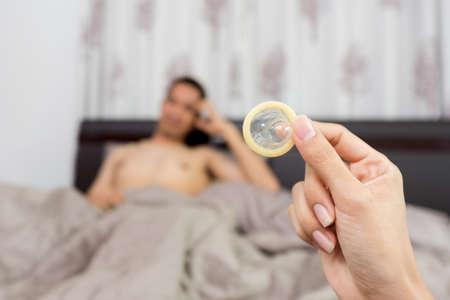 ベッドの上のコンドームを見せて女性フォア グラウンドでコンドームに焦点を当てる
