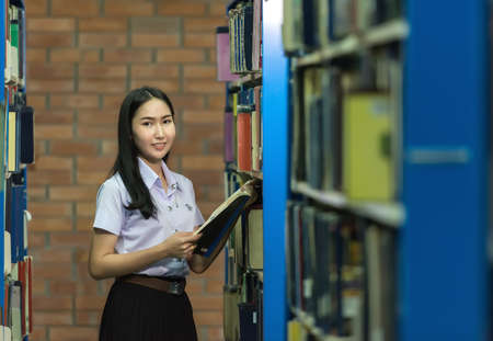 thai student: Woman students are a handful of books The bookshelf in the library Stock Photo