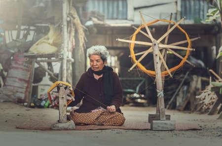 old women: Old women demonstrate to procedure of making Thai Silk weaving