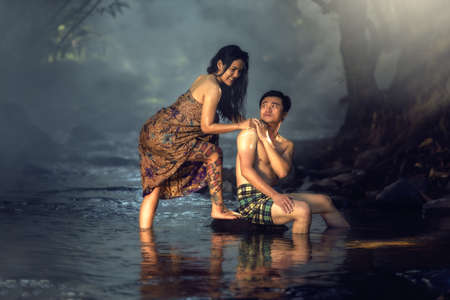 lying in bathtub: Asian couple bathing at cascade in Thailand countryside