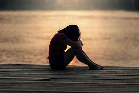 mirada triste: Mujer triste silueta preocupado al atardecer Foto de archivo