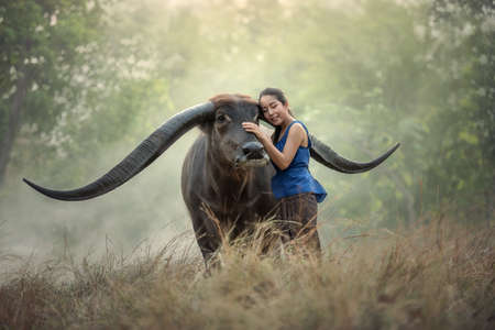 familias felices: granjero tailandés de la mujer con el búfalo