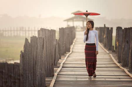 Burmese woman holding traditional red umbrella and walking on U Bein Bridge 스톡 콘텐츠