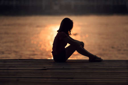 Sad woman silhouette worried at sunset Foto de archivo