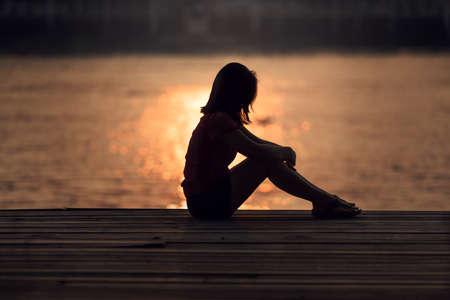 Smutna kobieta sylwetka martwi o zachodzie słońca