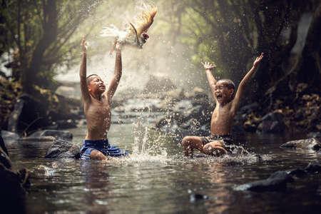 Chłopcy gry z ich kaczki w potoku Zdjęcie Seryjne