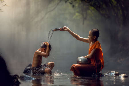 Little monk and child taking a bath at waterfall, Nong Khai, Thailand.
