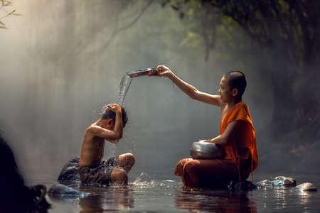 Pequeño monje y el niño toma un baño en la cascada, Nong Khai, Tailandia.