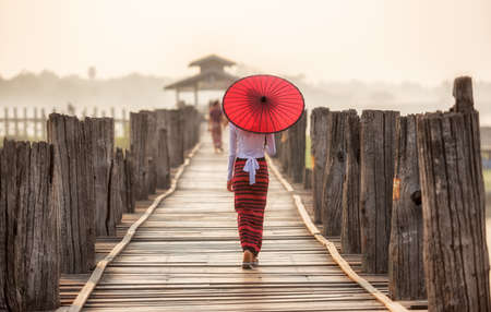 Burmese woman holding traditional red umbrella and walking on U Bein Bridge 版權商用圖片