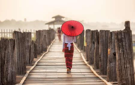 Mujer birmana que sostiene el paraguas rojo tradicional y caminar sobre U Bein Bridge Foto de archivo