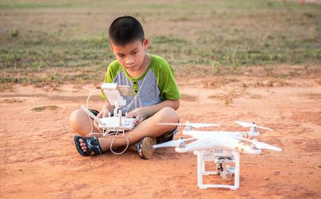 Porträtt av barn med quadcopter drönare utomhus. Lycklig pojke leker med flygande drönare med kameran kontrolleras av smartphone