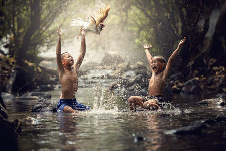 Boys playing with their duck in the creek
