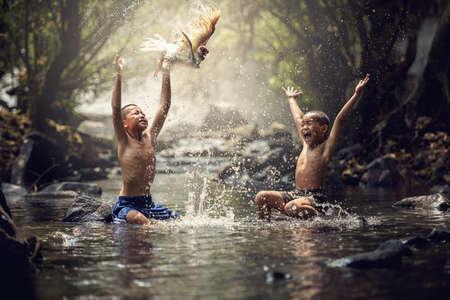 viaje familia: Niños que juegan con su pato en el arroyo