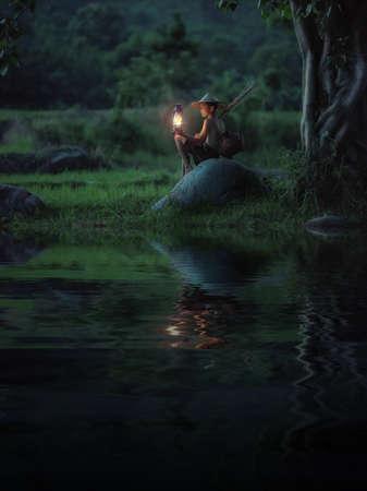 少年はランプを保持しています。人生の抽象的な意味願っています。 写真素材
